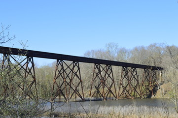 Landscape photo of a rusty train trestle crossing over a small lake in the woods