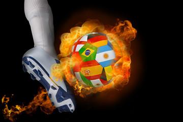 Football player kicking flaming international flag ball against black