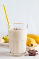 Spoed Foto op Canvas Fresh Made Chocolate Banana Smoothie on a wooden table. Selective focus. Milkshake with almonds. Protein diet. Healthy food and drink concept.