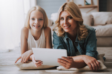 Mature blond woman with cute daughter watching tablet while lying on floor.