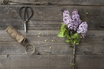 Overhead view of flowers with string and scissors on wooden table