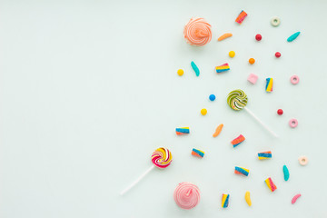 Colorful candies on pastel turquoise background. Flat lay, top view