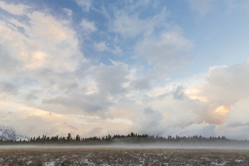 Scenic view of landscape against cloudy sky at Grand Teton National Park during sunset