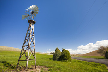 American-style windmill on hill against blue sky during sunny day