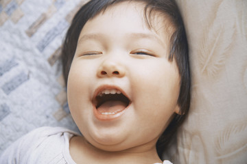 Close-up of playful girl with mouth open winking while lying on bed at home