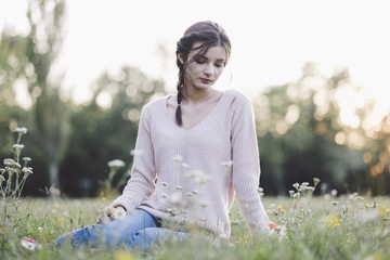Thoughtful young woman sitting on grassy field at park