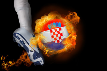 Football player kicking flaming croatia ball against black