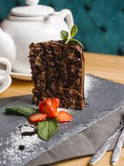 Close-up of chocolate cake slice on slate