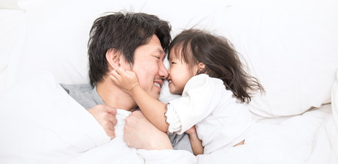 Father and daughter laughing and bonding in bed. Daddy and his little girl spending time at home. Fun love father's day family lifestyle concept banner
