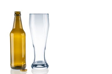 Empty beer bottle and tumbler on white background