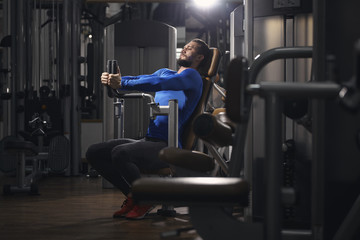 Man stretching on exercise machine at gym