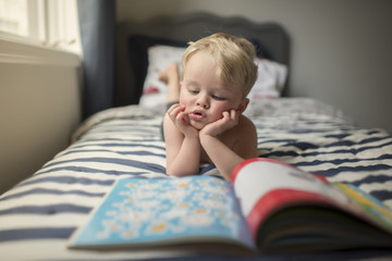 Boy with hands on chin reading picture book while lying on bed at home