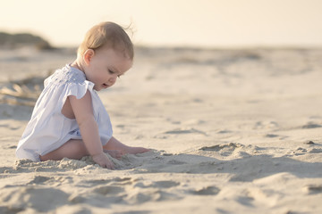 Side view of baby girl sitting on sand at beach against sky during sunset Wall mural