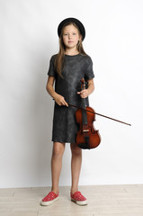 Portrait of girl holding violin while standing by wall at home