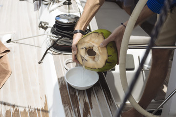 Cropped image of man pouring coconut water in bowl while traveling on boat