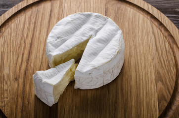 Cheese wheel on wooden board