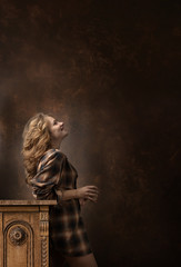 Pretty woman with long blonde hair in brown plaid shirt holds coffee cup and looks up .