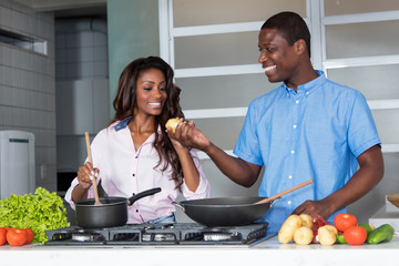 Laughing african american love couple cooking at kitchen