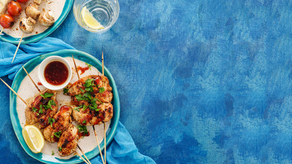Chicken kebab on skewers with cherry, mushrooms and barbecue sauce on a blue background