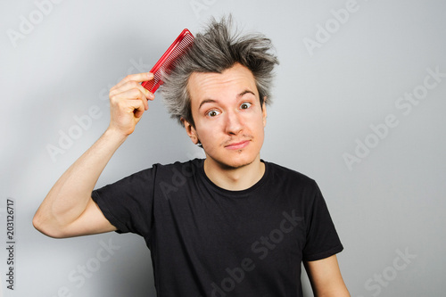 Unshorn And Unshaven Young Guy Combing His Hair On Gray