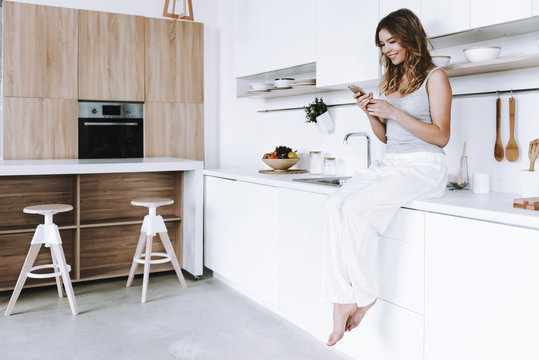 Cheerful woman with smartphone is sitting in kitchen.