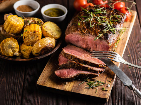 Sliced Roast beef on cutting board with grilled vegetables .