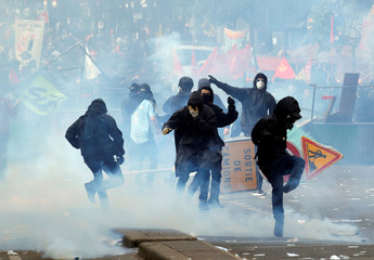 Tear gas floats around masked protesters during clashes with French CRS riot police at the May Day labour union rally in Paris