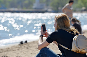 Woman with phone sitting on the beach among people and looking at smartphone