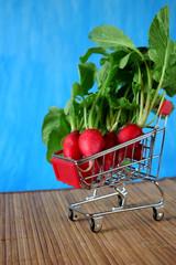 Fresh radish in a trolley on blue background. Copy space