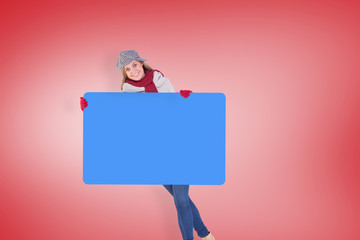 Happy blonde in winter clothes showing card against red vignette