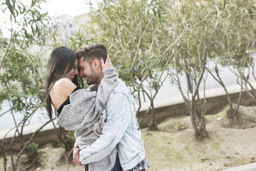 Young attractive couple in hug embracing in outdoors shot