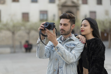 Young couple taking pictures in city outdoors at european travel
