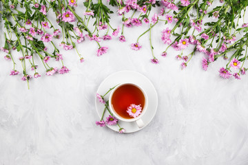 Cup of black tea with pink daisy flowers on cement background, flatlay