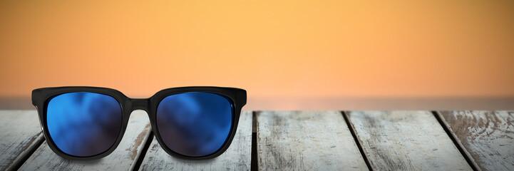 Close-up of sunglasses against waves crashing at sunset Wall mural
