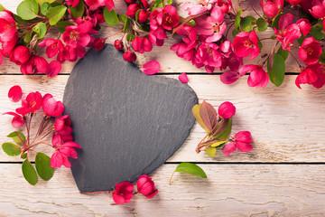 Herz aus Schiefer und Blüten auf Holz