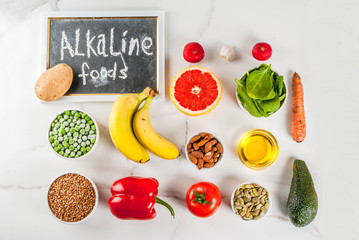 Healthy food background, trendy Alkaline diet products - fruits, vegetables, cereals, nuts. oils, white marble background above copy space