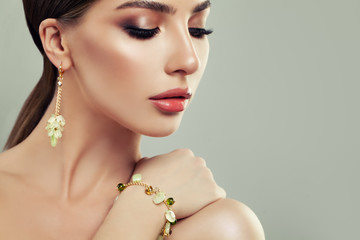 Closeup Portrait of Young Woman with Jewelry. Female Face with Makeup, Gold Bracelet and Earrings with Green Gem