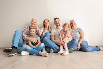 Happy family with cute kids sitting on floor near light wall