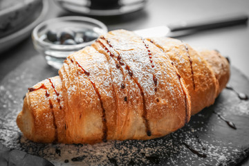Tasty croissant with sauce and sugar powder on slate plate, closeup