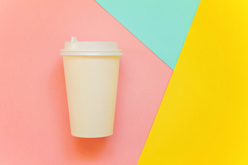 Paper coffee cup on blue, yellow and pink pastel colorful paper geometric flat lay background. Takeaway drink container. Template of drink cup for your design for put text, image, and logo mockup