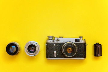 Vintage film photo camera lens film roll and accessories on yellow colourful trendy modern fashion pin-up background. Technology development photographer hobby classic memory trip concept. Top View