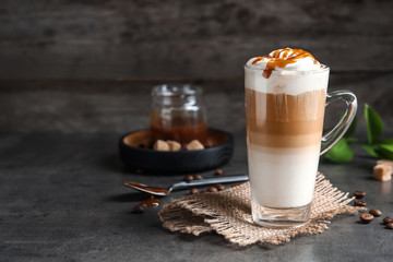 Glass cup with delicious caramel frappe on table