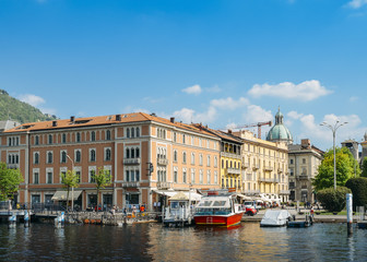 View of the city of Como, including boats on the marina and traditional colours buildings on the waterfront of Lake Como.