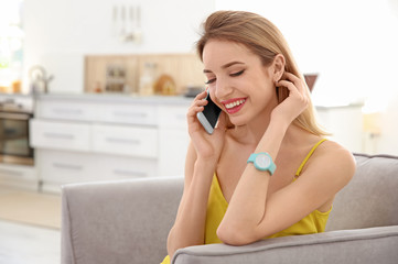 Young woman talking on phone indoors