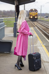 the woman in a pink raincoat at the railway station