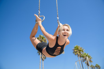 Pretty healthy blonde woman working out and having fun by the beach with a fitness tracker