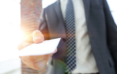 Businessman giving a card. Close-up photo in loft office