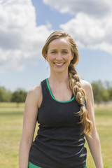 Portrait of smiling mid adult sporty woman with braided hair standing at park