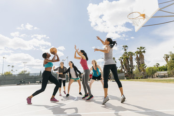 Young women playing basketball on court