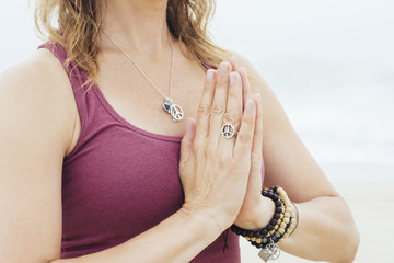 Mature woman with hands clasped doing meditation at beach